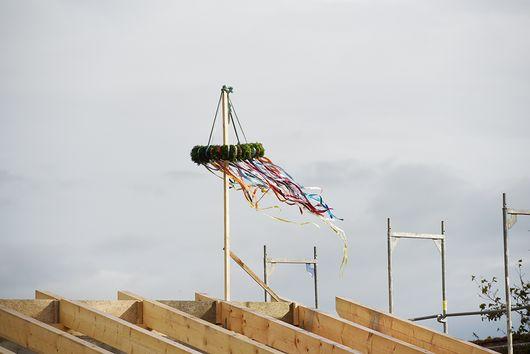 Geschmückter Richtkranz auf Dachstuhl wehend im Wind