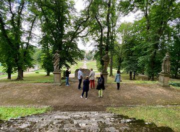 Mehrere Personen stehen unterhalb einer Treppe und schauen auf den weiter unten liegenden Schloßgarten von Ebeleben hinab.
