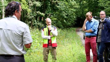 Staatssekretär Torsten Weil unterhält sich am Rande einer Waldweges mit Forst-Experten