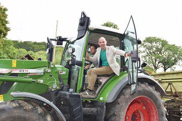 Staatssekretär Weil sitzt im Traktor und schließt die Tür zur Losfahrt