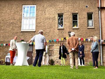 8 Personen stehen im Kreis auf einer Wiese vor einer älteren Hausfassade