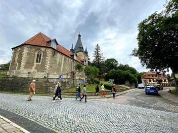 Mehrere Personen laufen über eine gepflastere Straße Richtung Kirche