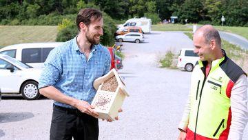 Staatssekretär Torsten Weil steht mit einem Mann etwas oberhalb eines geschotterten Parkplatzes. Der Mann freut sich und hält in seinen Händen ein kleines Insektenhotel aus Holz.