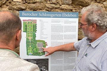 Staatssekretär Torsten Weil betrachtet mit einem Mann eine Hinweistafel zum Schlossgarten Ebeleben. Die Hinweistafel ist an eine alte Mauer angebracht. Der Mann zeigt mit der Hand auf der Hinweistafel auf eine grafische Darstellung des Schlossgartens.