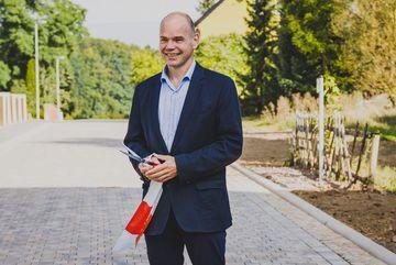 Staatssekretär Torsten Weil mit Schere und Teil des Absperrbandes