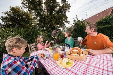 Familie sitzt im Garten eines Dorfes am Holztisch mit regionalen Produkten