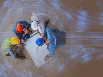 Symbolisches Bild: Vier Ingenieure mit Bauarbeiterhelmen neigen sich über Plan zu Straßenbauprojekt