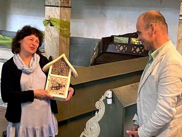 Staatssekretär Torsten Weil steht lachend mit einer Frau (Mitglied der Kirchengemeinde) im inneren der Kirche. Die Frau hält ein Bienenhäuschen auf Holz in den Händen und freut sich.
