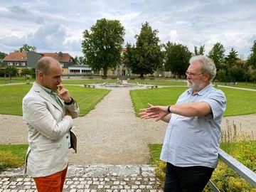 Staatssekretär Torsten Weil unterhält sich mit einem Mann. Der Staatssekretär hört dem Mann ausmerksam zu. Der Mann erklärt etwas. Im Hintergrund ist der Schlossgarten mit Wiesenflächen und einem barocken Brunnen zu stehen.