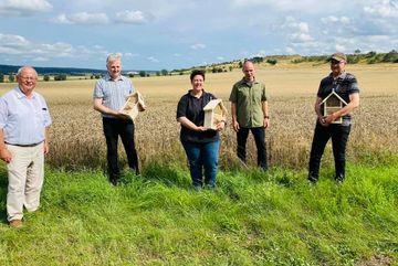 Im Vordergrund stehen fünf Personen am Rand eines großen Getreidefeldes und schauen in die Kamera.