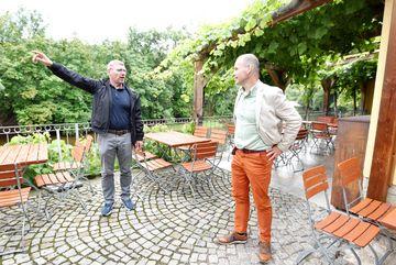 Besuch des Weingutes Zahn - mit Natursteinen gepflasterter Biergarten, im Hintergrund eine mit Wein bewachsene Pergola, im Vordergrund Staatssekretär Weil im Gespräch mit einer Person