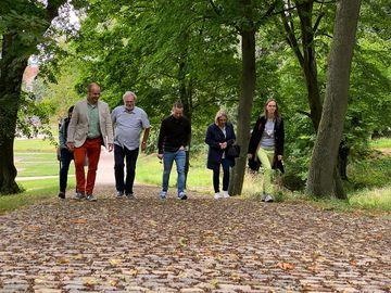 Mehrere Personen laufen durch den Schlossgarten Ebelebens und sprechen miteinander
