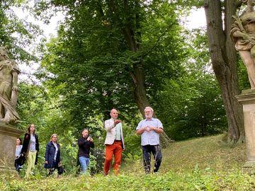 Mehrere Personen laufen durch den Schlossgarten Ebelebens und sprechen miteinander.