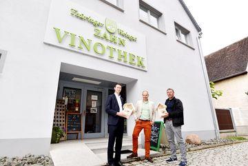 Staatssekretär Torsten Weil steht mit 2 Mitarbeitern des Weingutes Zahn vor dem Eingang der Vinothek. Die Mitarbeiter halten jeweils ein Insektenhotel in den Händen. Alle schauen in die Kamera.