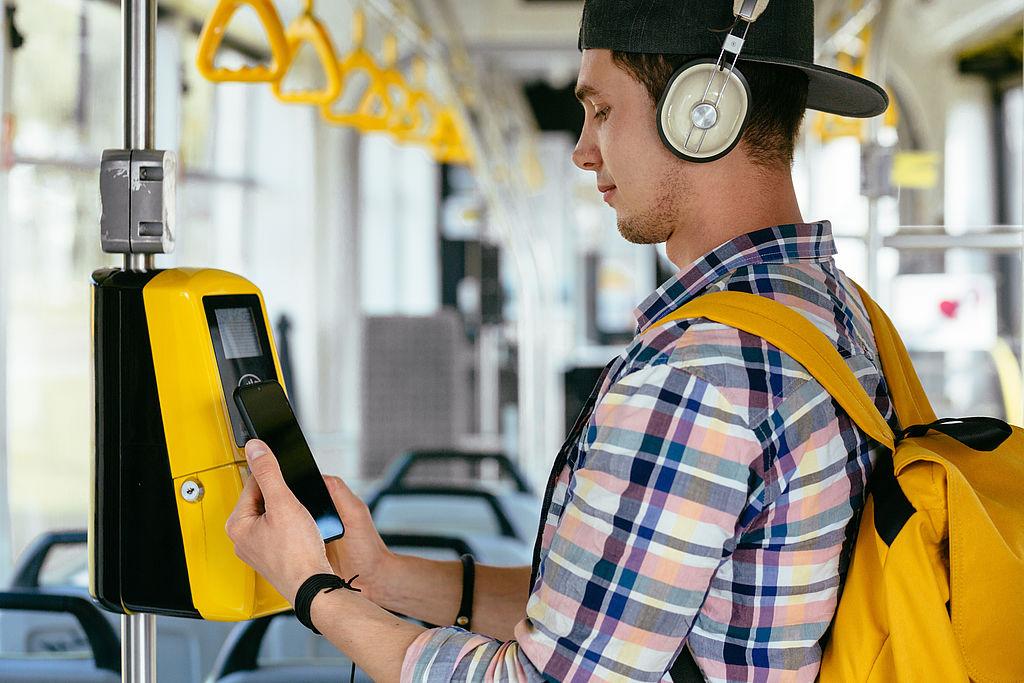 Jugendlicher beim Online-Check in einem Nahverkehrsbus