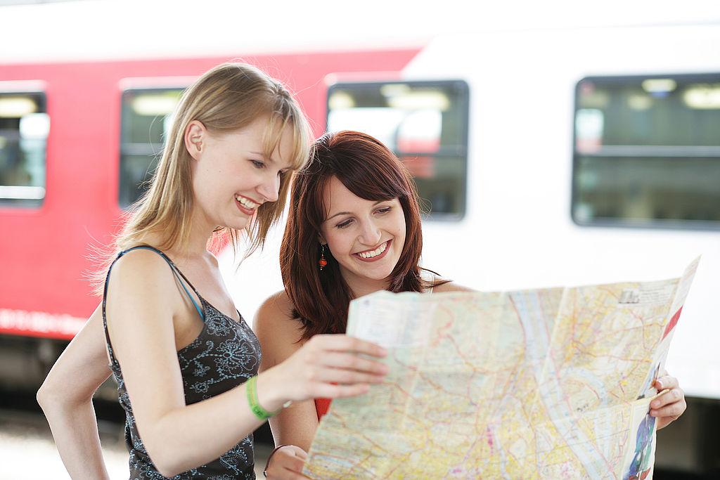 Junge Frauen informieren sich mit einer Bahnstreckenkarte